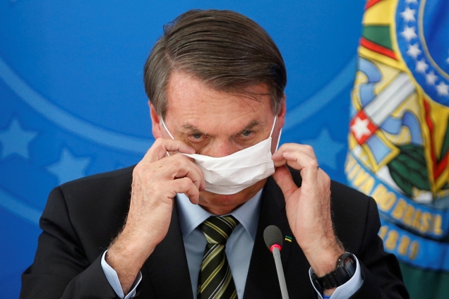 Brazil's President Jair Bolsonaro wearing a protective face masks reacts during a news conference to announce measures to curb the spread of the coronavirus disease (COVID-19) in Brasilia
